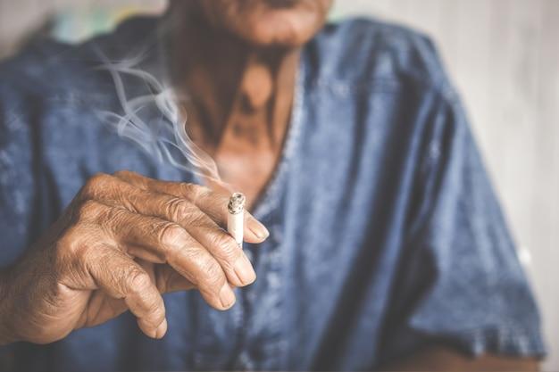 アジアの古い男性の手がタバコのスモーキンを保持