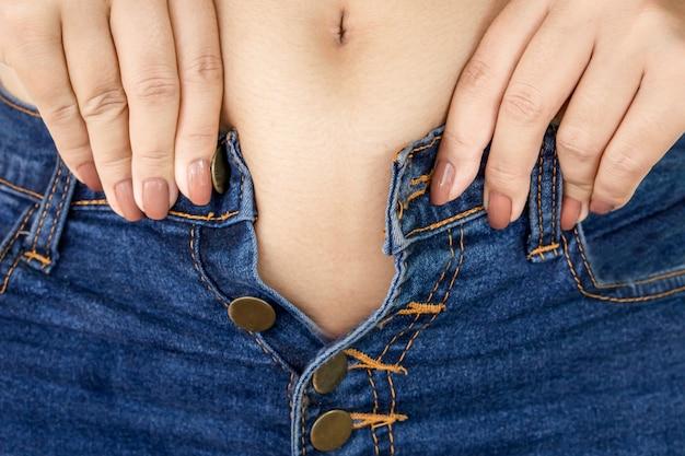 太った女性がタイトなジーンズを着用しようとする