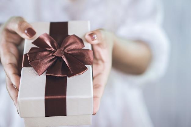 クリスマスの日にギフトボックスを与える女性の手