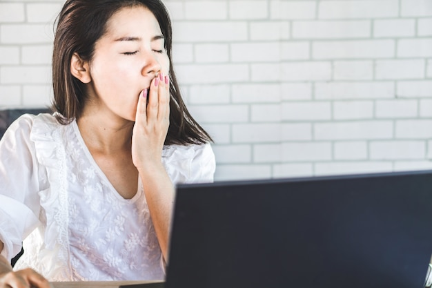 Уставшая азиатская женщина зевая на рабочем месте
