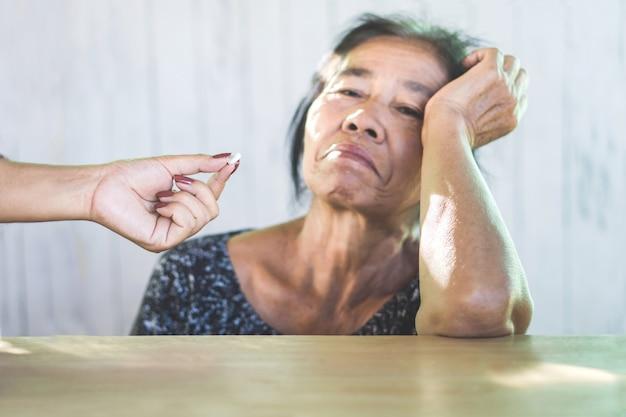 不幸なアジアの母親は薬の服用を拒否します