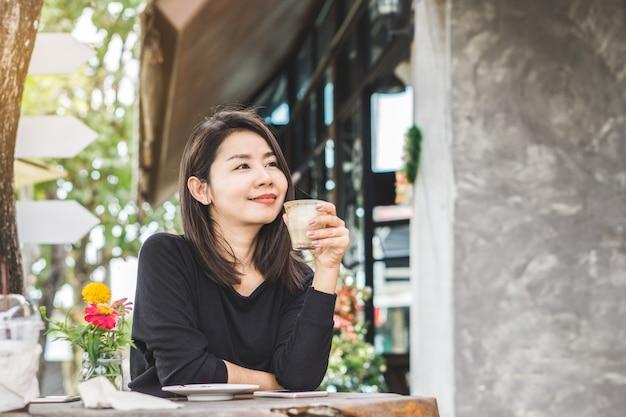 美しいアジアの女性が屋外でコーヒーを飲む