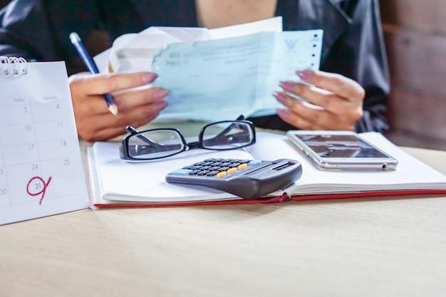 ビジネスの女性が彼女の毎月の請求書を計算します。