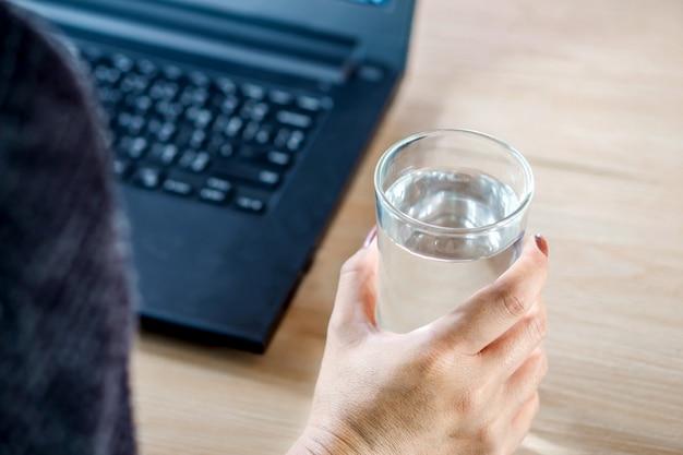Женщина пьет воду, работая на компьютере