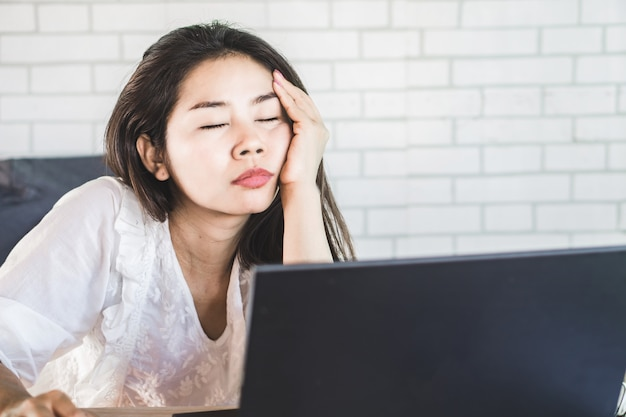 Утомленная азиатская женщина сонная на работе