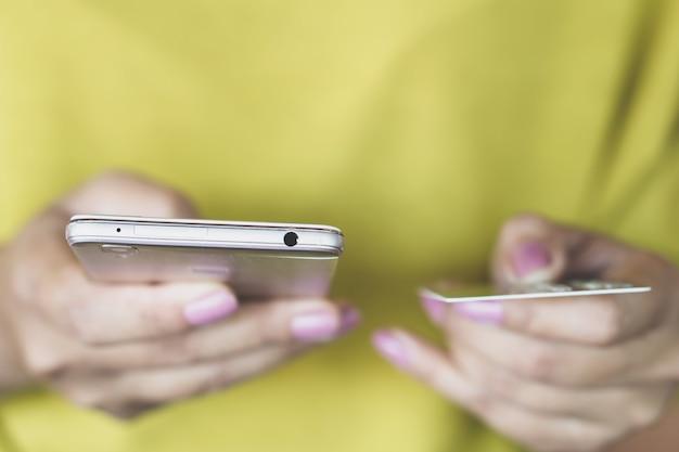 オンラインショッピングのためのクレジットカードとスマートフォンを持つ女性の手