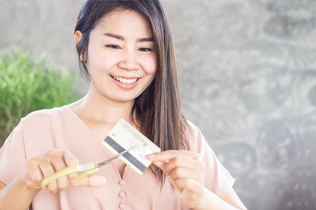 幸せなアジア女の手がハサミでクレジットカードを切る