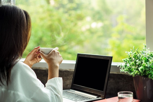 Деловая женщина пьет кофе в домашнем офисе