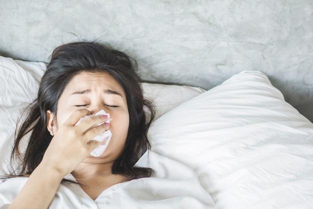 アジアの女性がインフルエンザとベッドでくしゃみをする