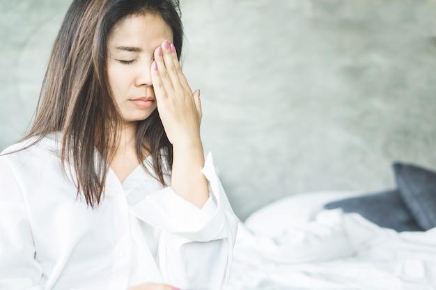Азиатская женщина имеет головную боль и боль в глазах от мигрени