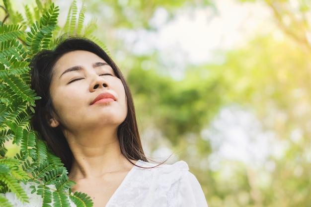 美しいアジアの女性が自然とリラックス
