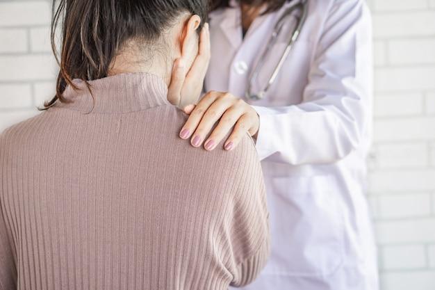 医師の手を慰めるストレス女性患者