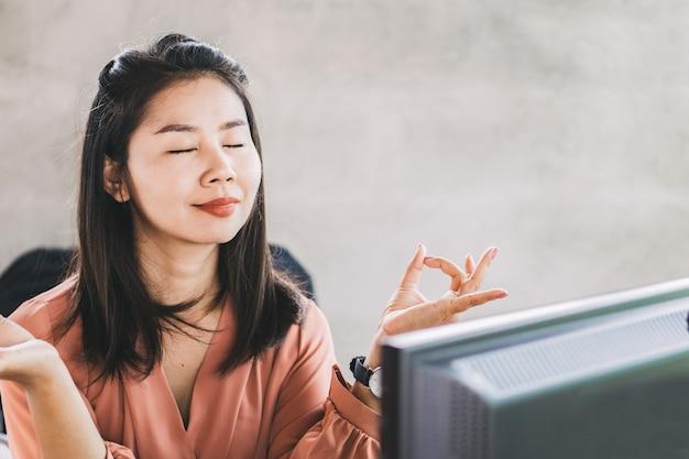 アジアビジネス女性のオフィスの机でヨガをやっています。