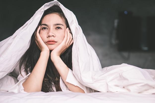 ベッドで疲れて眠れないアジアの女性
