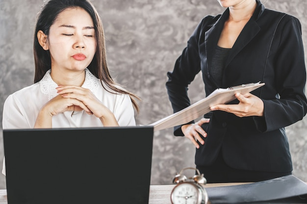 退屈しているアジアの女性従業員は、迷惑な上司を無視します