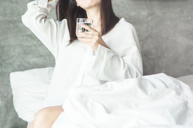 朝は新鮮な水を飲む女性