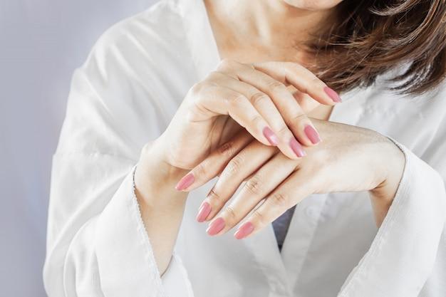 Крупным планом красивая женщина руками палец, лак для ногтей