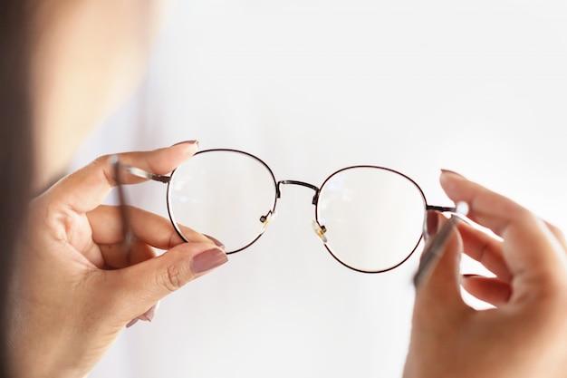 眼鏡のクローズアップを持つ女性の手