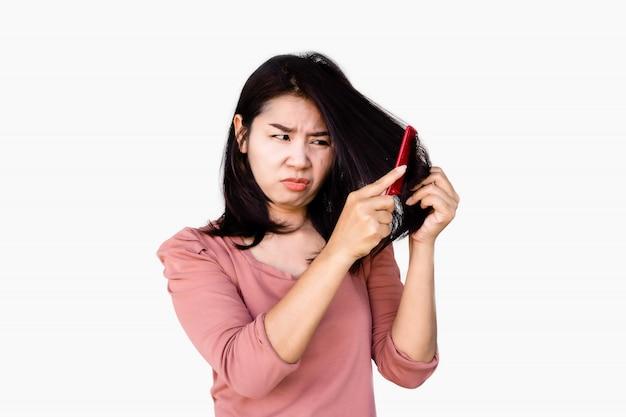 Несчастная азиатская женщина используя расческу расчесывала ее поврежденные длинные волосы