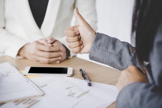 Женский босс счастлив и согласен с проектом, показывающим руку, как в команде