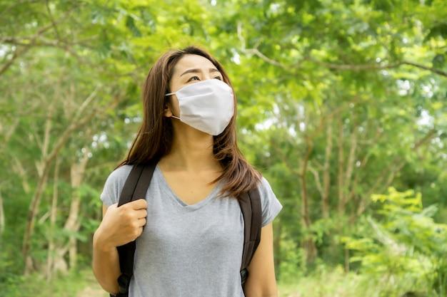 防護マスクを着て公園を旅行するアジアの女性観光