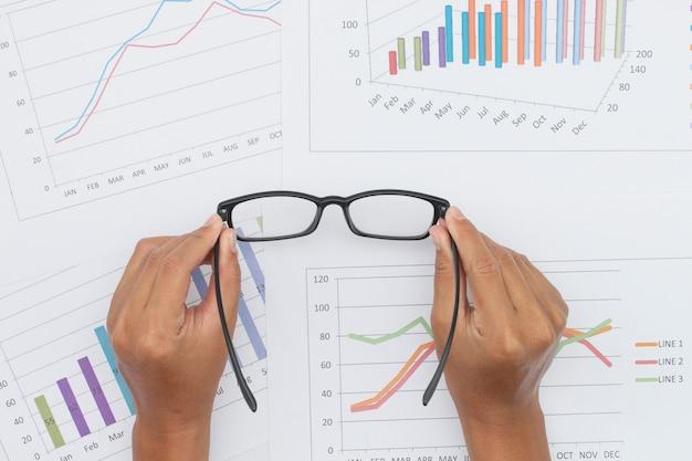株式市場レポートとメガネを持っている手
