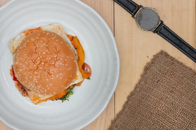 ハンバーガー、木製テーブルに腕時計。