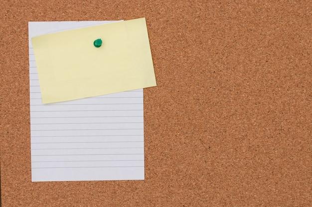 コルクボードの背景にプッシュピンとメモ用紙。
