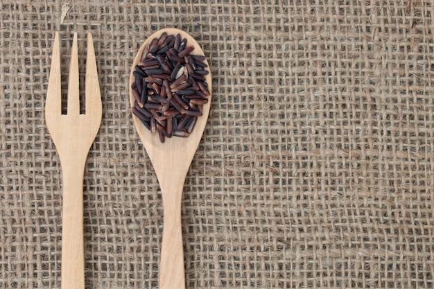 トップビュー:袋のテクスチャに木のスプーンで玄米(ライスベリー)。