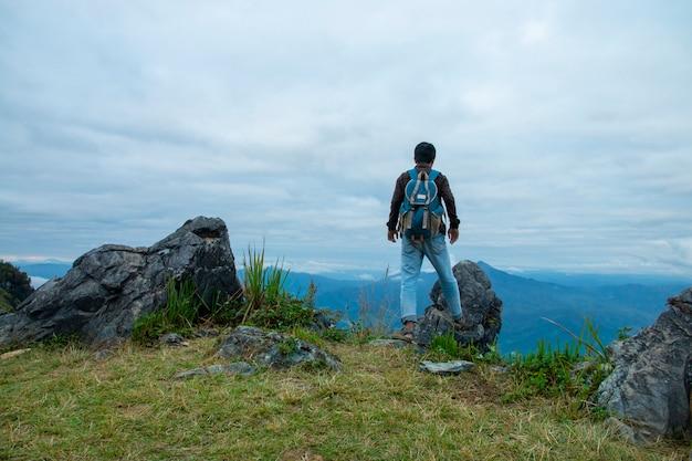 崖の上に立っていると日光の下で谷や山々を見ている男