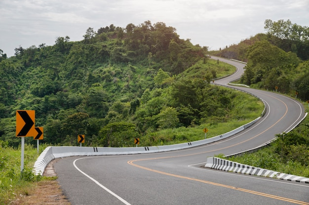 山のサイン曲線と曲線のアスファルト道路。