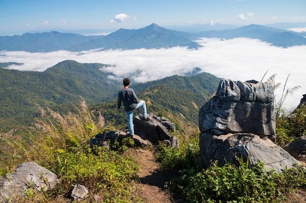 Человек стоит на скале и смотрит на долину и горы в дневное время