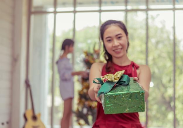 アジアの女性は、パーティーで彼女の友人に贈り物を開催し、表示する