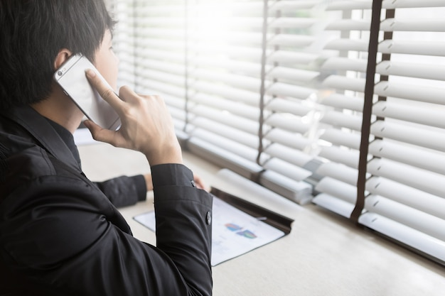Деловой человек, выступая на мобильный телефон на рабочем месте