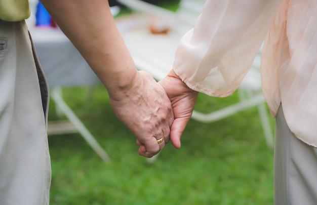 年配のカップルが自宅の庭で一緒に手を繋いでいます。
