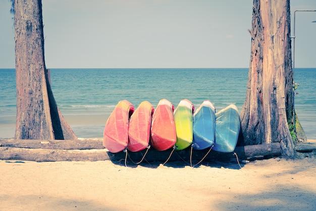 熱帯のビーチでカヤックボートのレトロなスタイルのスタック。夏休み。