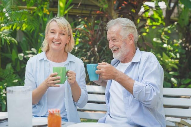 家の庭で朝のコーヒーを飲みながらリラックスした幸せな先輩カップル
