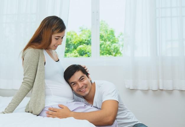 Счастливый муж слушает ребенка в живот беременной жены в спальне у себя дома