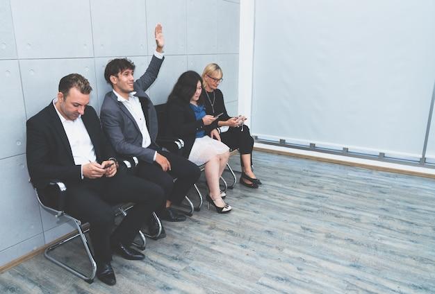 ビジネスの男性が彼の手を上げて就職の面接の準備ができている間他のビジネス人々はスマートフォンを使用して