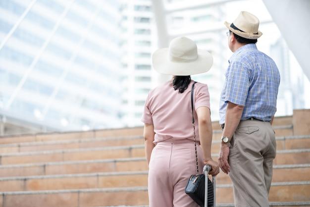 幸せなアジアカップルシニア観光客が旅行中にシティービューホールドスーツケースハンドルを探している