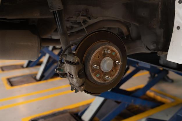 車の自動車修理工場で新しいタイヤの交換を準備するタイヤのない車のホイール