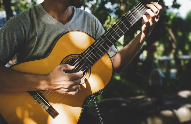 公園でクラシックギターを弾く男