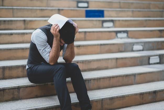 階段に座っている間彼の頭に置かれた終了契約の通知を保持しているビジネスマンを強調