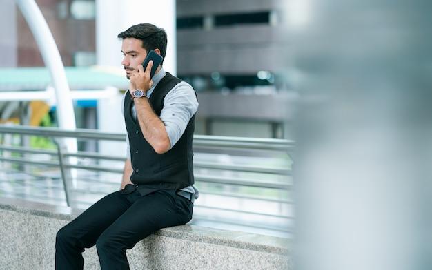 Красивый бизнесмен сидит и звонит на мобильный телефон снаружи