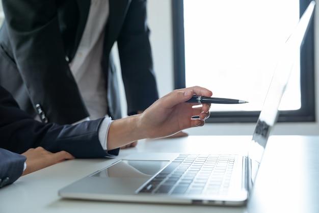 ペンを使用してアジアの若い実業家がラップトップでマーケティングビジネスプランを指し、職場のマネージャーを表示する