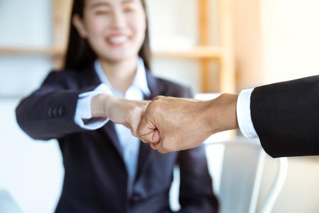 オフィスで一緒に仕事の成功の後、彼女のボスとアジアの若い実業家バンプ拳を笑顔します。チームワーク成功のコンセプト