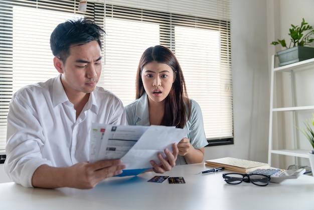 電気代などの非常に多くの費用の請求書を探しているカップルの若い家族の夫と妻のストレス