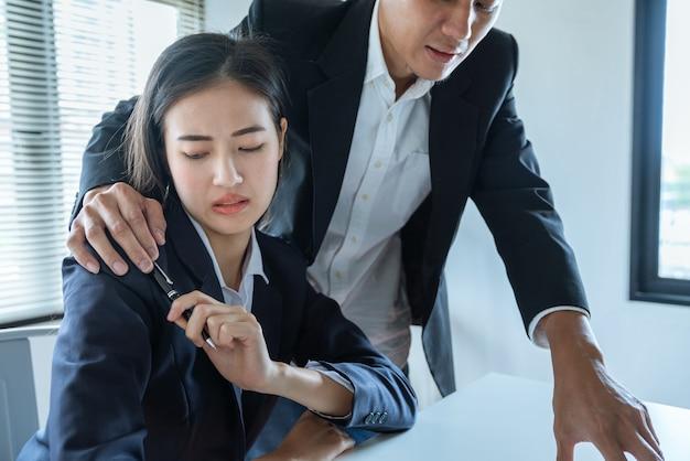 アジアビジネスの男性は彼の手を抱擁同僚女性を使用して、オフィスでの仕事、性的暴行および嫌がらせの概念を説明します