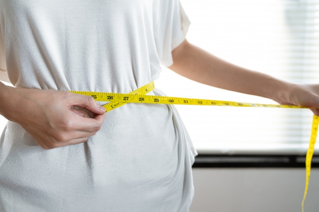 Молодая азиатская женщина используя ленту измерения измеряя ее талию после попыток теряет вес с ест здоровую еду.
