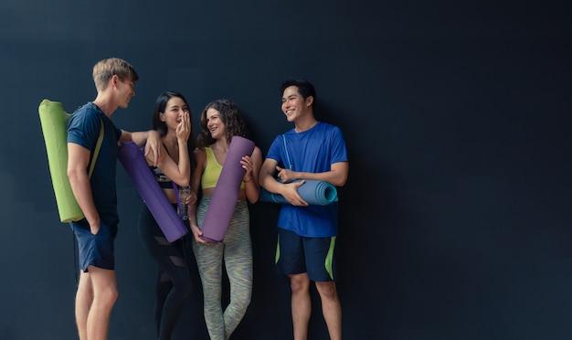 若い男性と女性のグループは立って話して楽しい時を過すし、ジムスポットクラブでのヨガの練習の前にヨガマットを保持